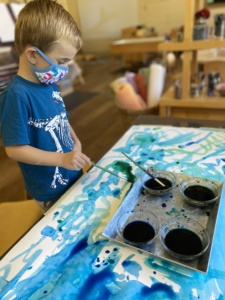 child painting with face covering