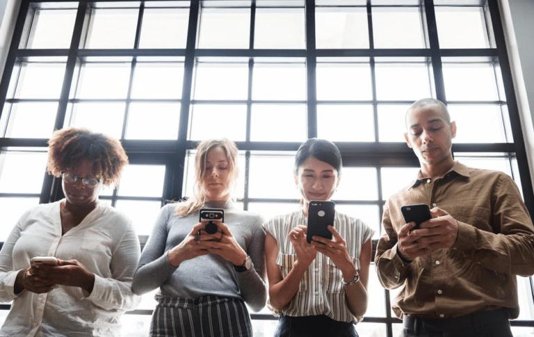 coworkers looking at phone screens
