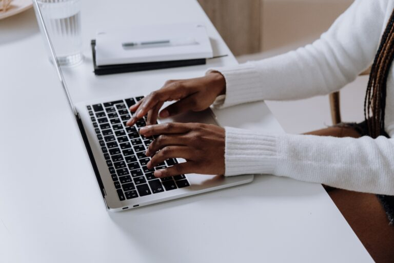 black woman in a white shirt typing on her macbook laptop.