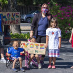 Francisco Garcia, son Nicolas and daughters Josie (seated) and Amaya (standing) display the signs the kids made before the march and car caravan. Along with wife Jennifer McInnis is Amanda McCarthy, both on Community Action Marin's Board.
