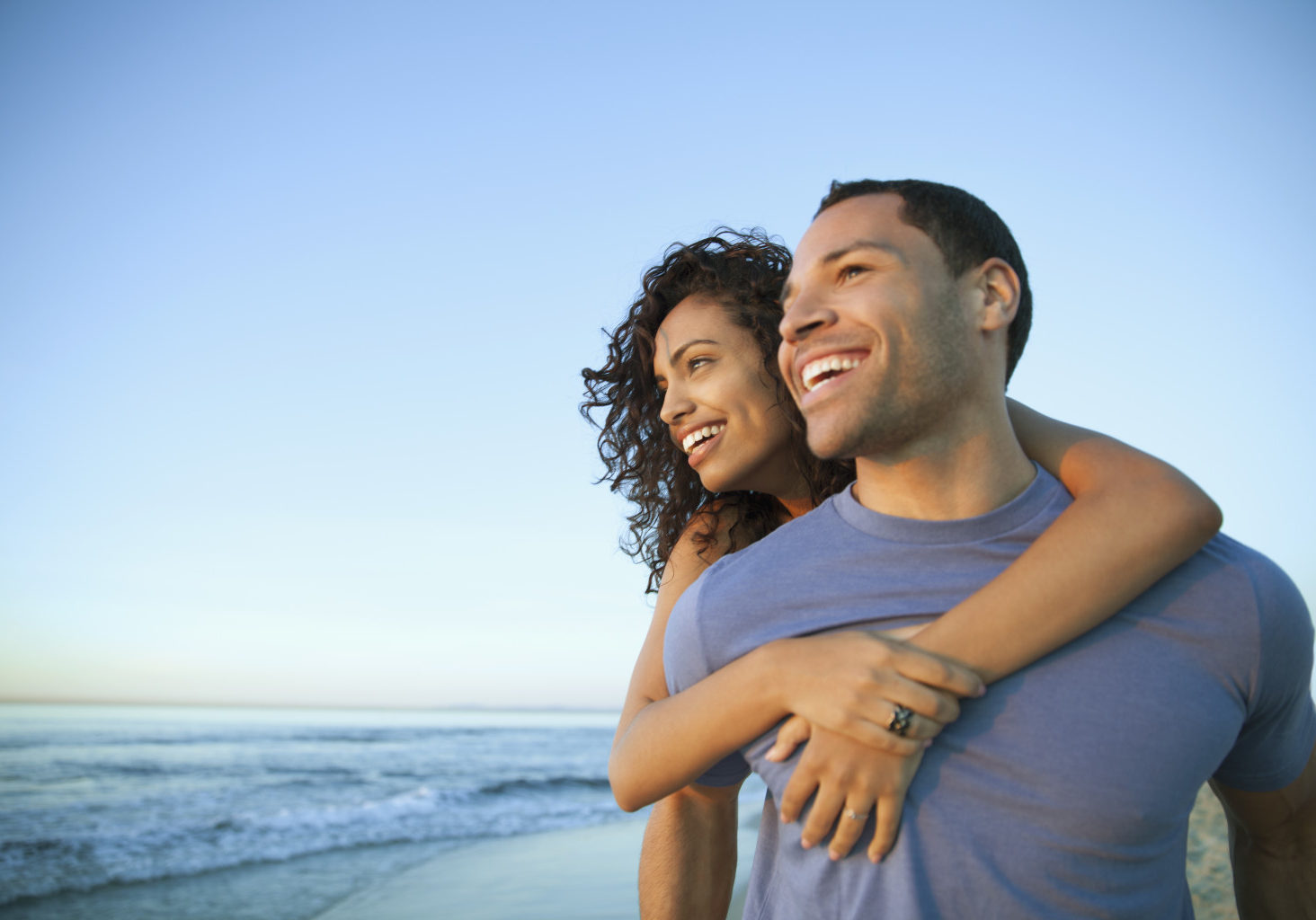Happy young man giving piggyback ride to woman while looking away at beach