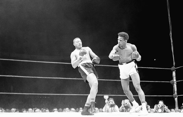 """(Original Caption) Big Bob Baker (left) leans back to evade the hurricane of blows from Tommy """"Hurricane"""" Jackson in the third round of their heavyweight go at the Garden tonight. Jackson won by a very close decision over his Pittsburgh opponent, who is regarded as the number two contender for the crown."""