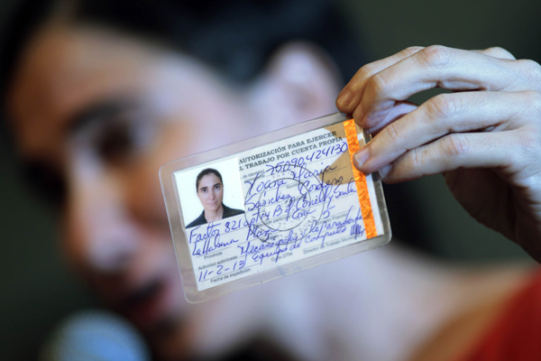 Cuba's best-known dissident, blogger Yoani Sanchez, shows her work permit which was issued by Cuba, during a news conference in Feira de Santana