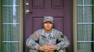 woman in military sitting in front of purple door
