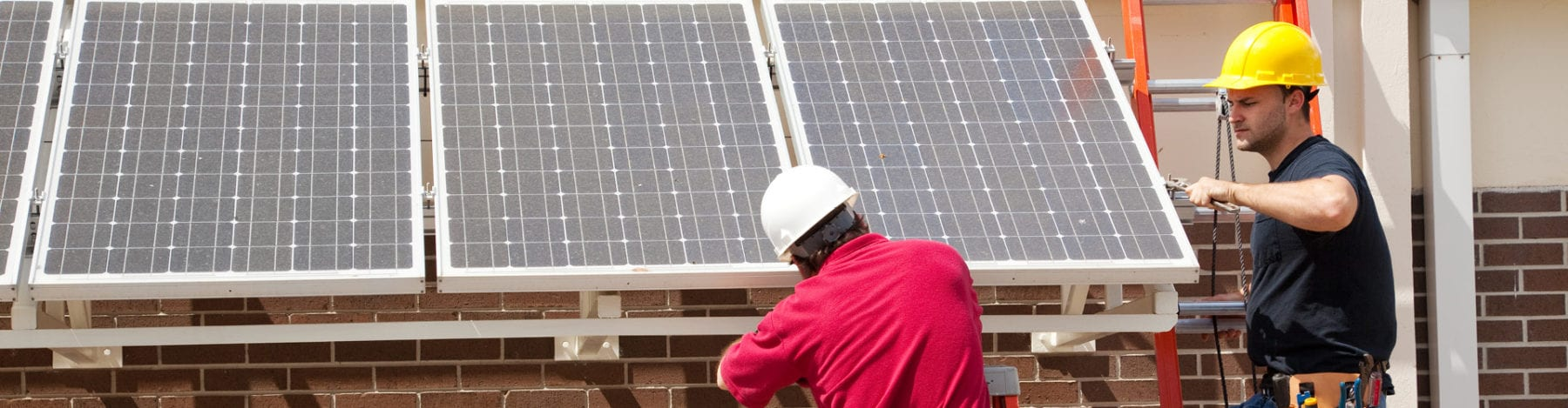 Two SunState Solar techs providing professional commercial solar energy systems installation services.