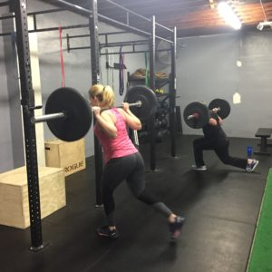 People doing barbell lunges