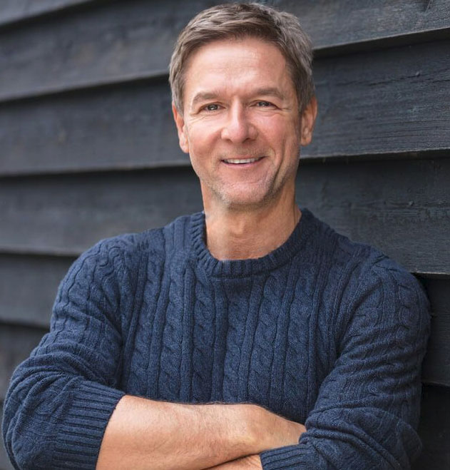 Middle-aged man leaning on wood siding