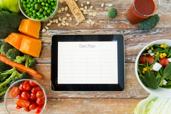 Close up image of tablet with diet plan on wooden table surrounded by healthy foods