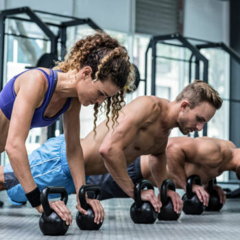 One female and two male, muscular athletes in a plank position using kettle bells