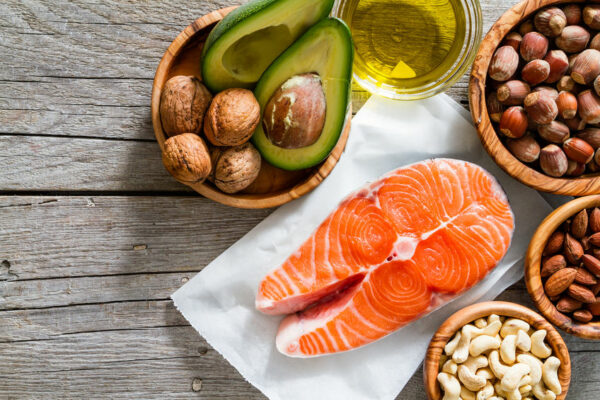 Healthy fat sources including salmon, nuts, and avacado on wooden table.