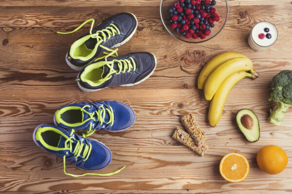 Top view of shoes and fruit on a wooden table.