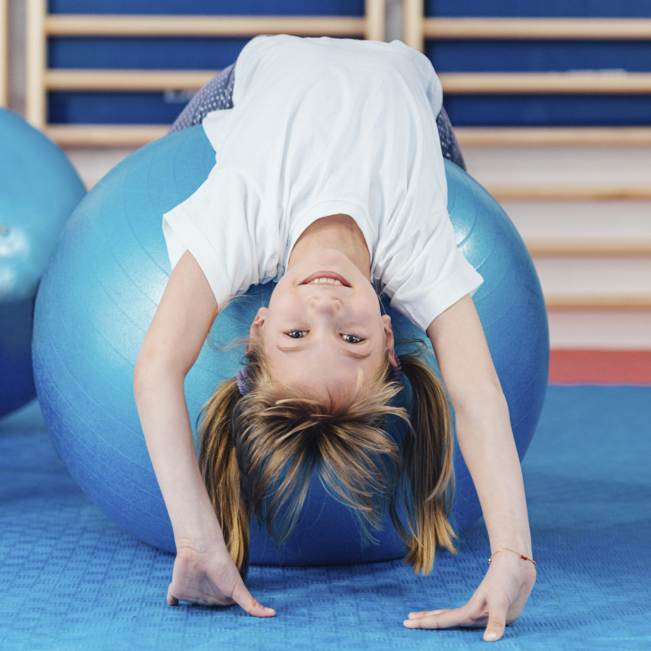 Cute girl exercising on pilates ball