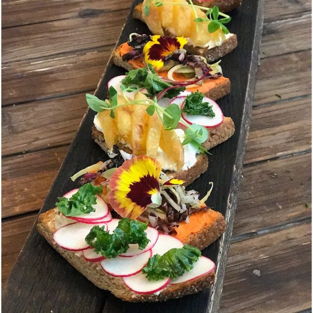 Serving board with a variety of small tartness garnished in colorful vegetables slices and a sprinkle of microgreens
