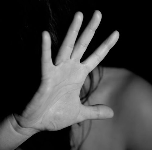 Fearful victim of domestic abuse with hand up for protection