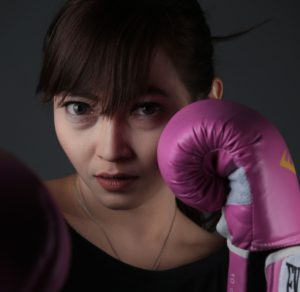 Woman with pink boxing gloves in defensive position to prevent narcissistic abuse re-victimization.