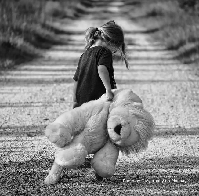 Image of sad child carrying a stuffed animal representing wounded inner child.
