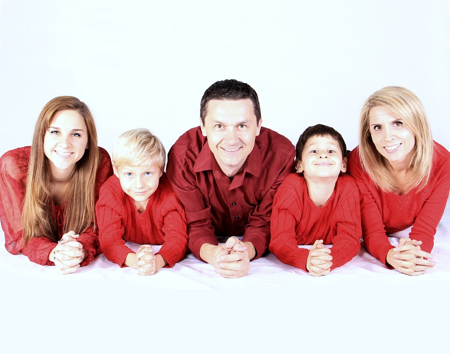 Family of five with red shirts on elbows smiling representing narcissistic family