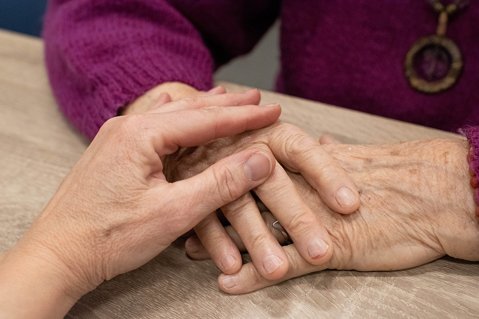 Hand touching the hands of an elderly person showing empathy
