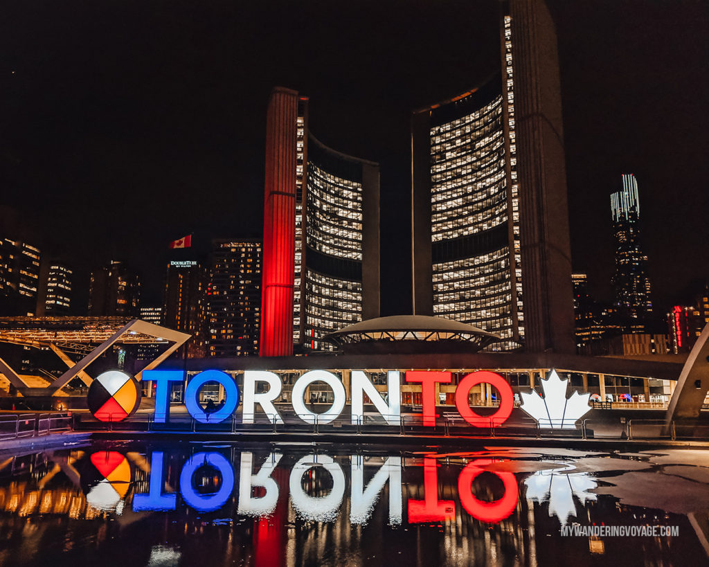 Reflection of the Toronto sign at Nathan Phillips Square at night | With the powerful device in your pocket you can take incredible photos of your travels. Here is the ultimate guide to smartphone travel photography. | My Wandering Voyage travel blog #travel #photography #tips #travelphotography #smartphonephotography