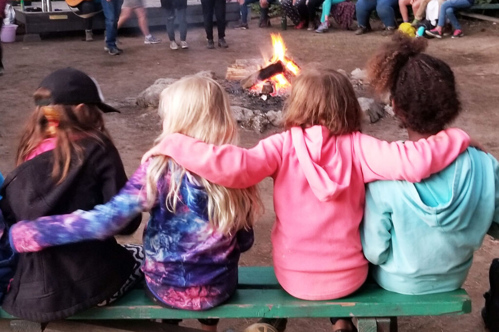 girls sitting together at the campfire
