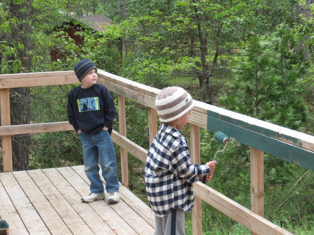 boys painting deck railing