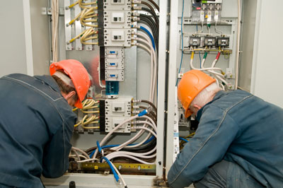 two electrical contractors wiring an industrial panel