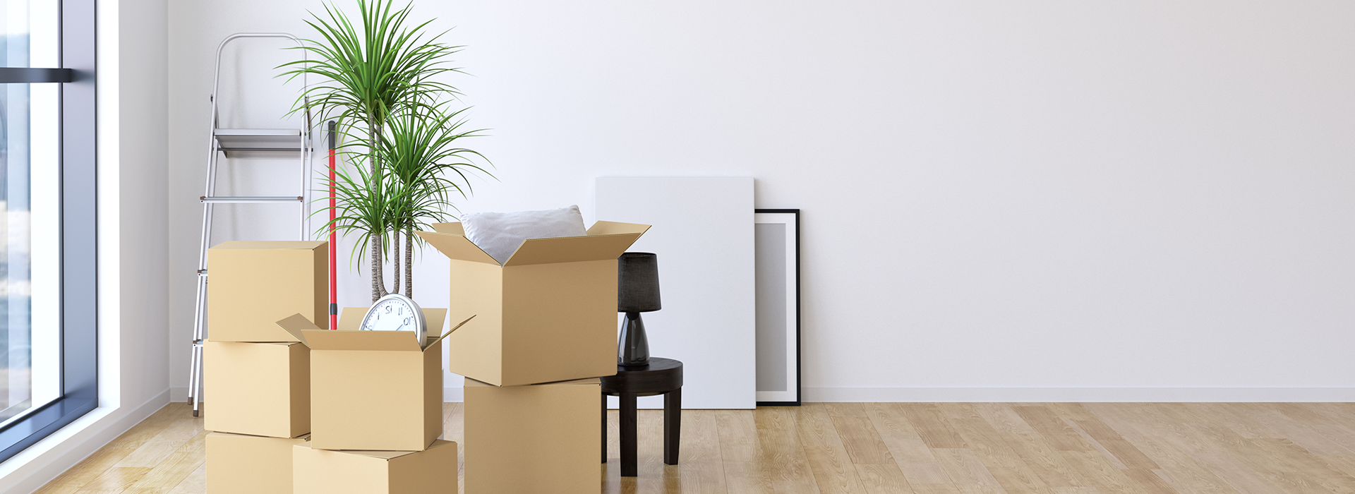 Furniture and Boxes stacked near a large window, they appear in the process of being packed in a white room with wooden floors.