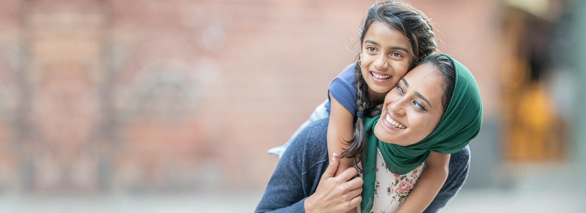 A mother wearing a green hijab with a small girl who has braids in her hair on her back.