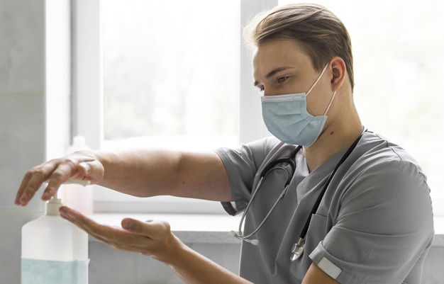 side-view-doctor-with-medical-mask-using-hand-sanitizer_23-2148735410