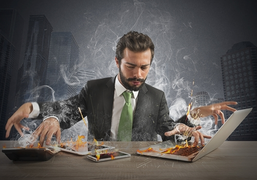 A stressed out entrepreneur who is working quickly with many different computers in a meeting room