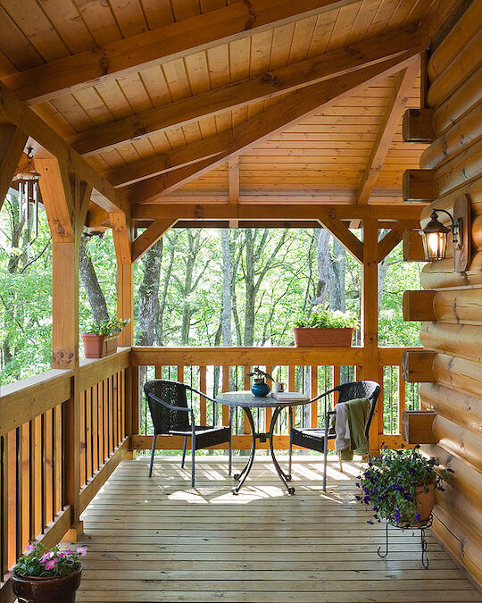 photo of log home front porch with chink trim, exposed wood ceiling ad rails