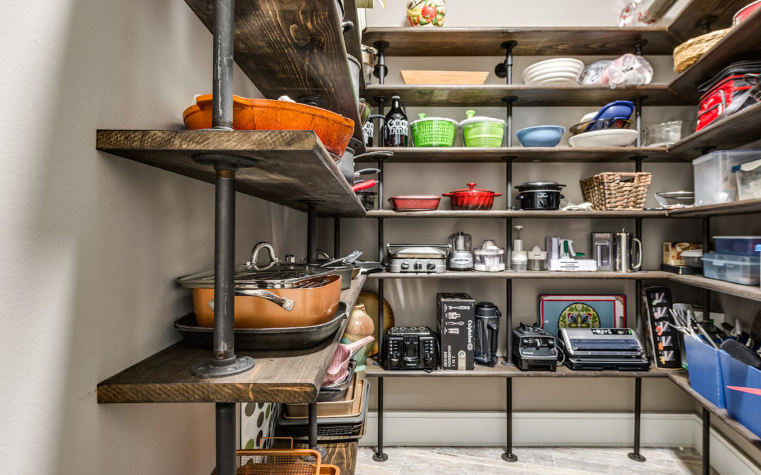 photo of large walk in pantry with shelving for oversized kitchen appliances and cookware