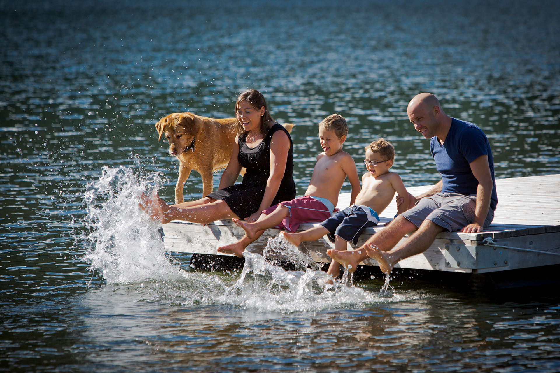 Family and dog on the dock while splashing their feet in the water