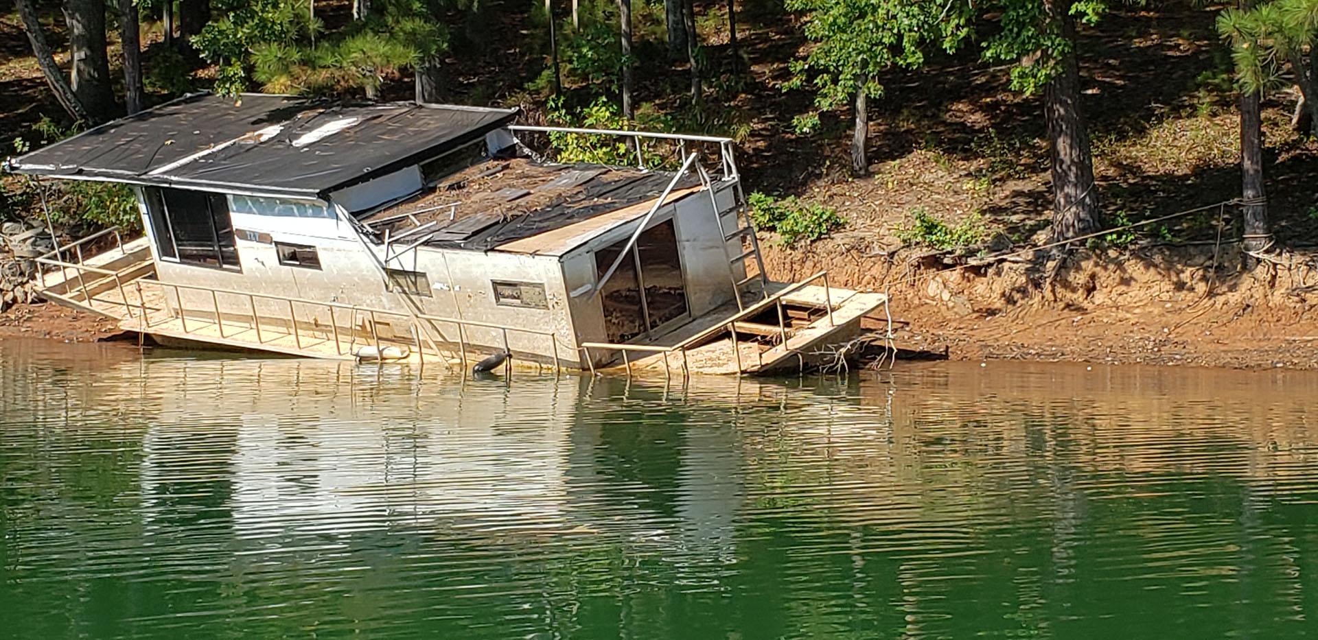 Large boat abandoned on the shore line of Lake Lanier