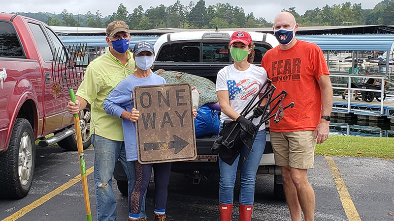 Family holds up trash collected during Shore Sweep