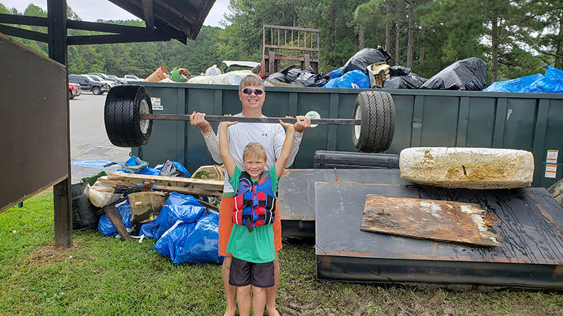Dad and sone showing what they collected at Shore Sweep