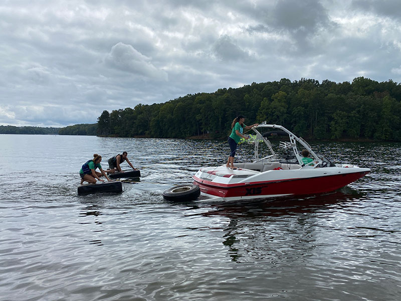 Shore Sweep volunteers removing tires from the lake