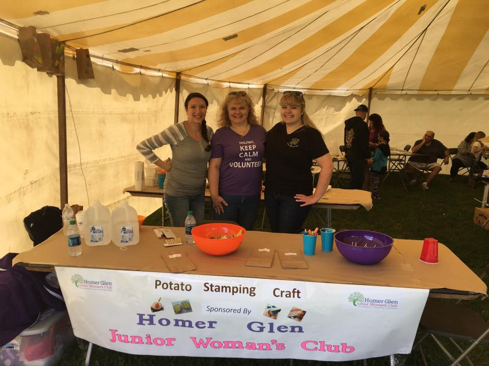 Art Committee Members volunteer at Homer Harvest Days with a kids craft