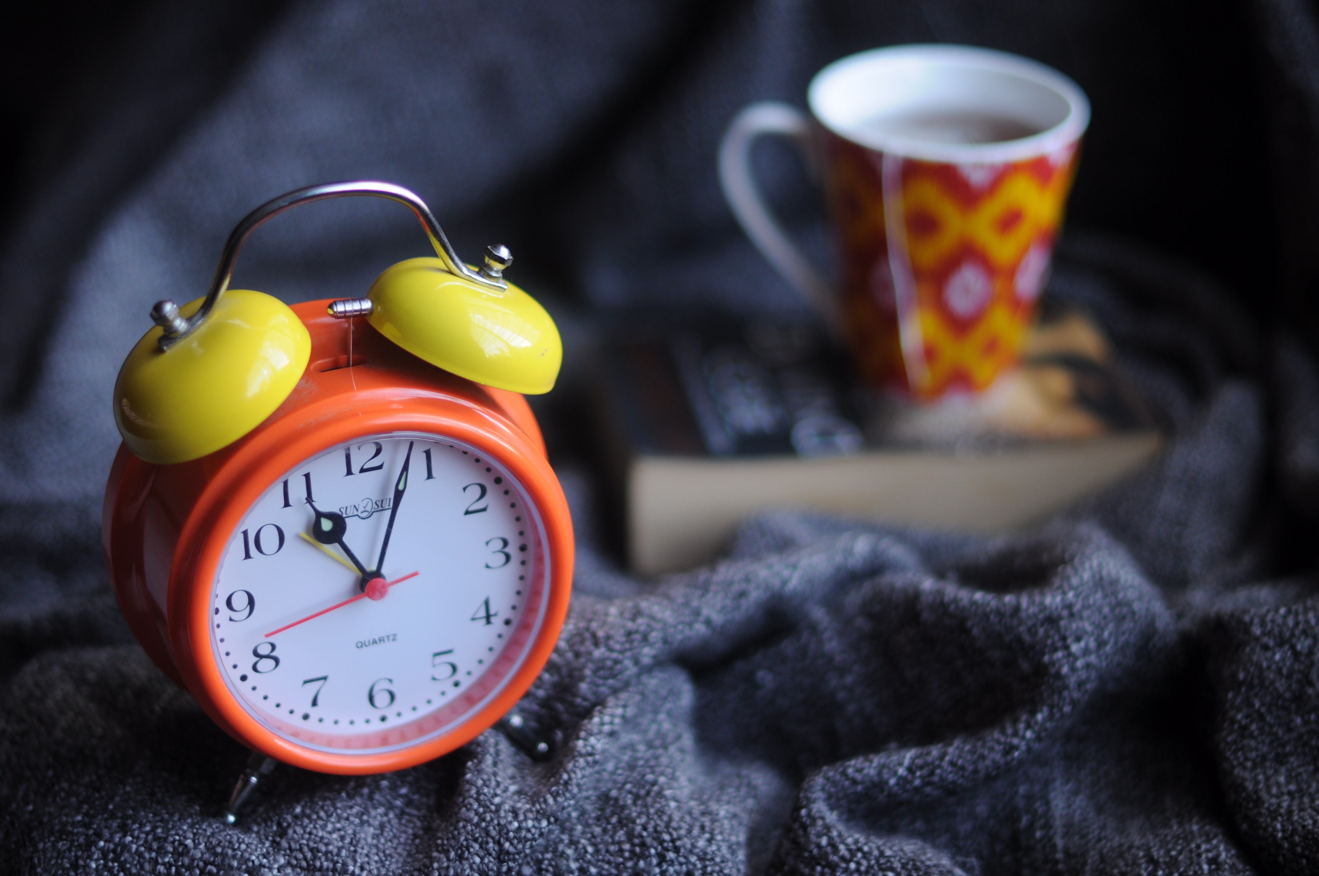 Alarm clock and hot drink on bed