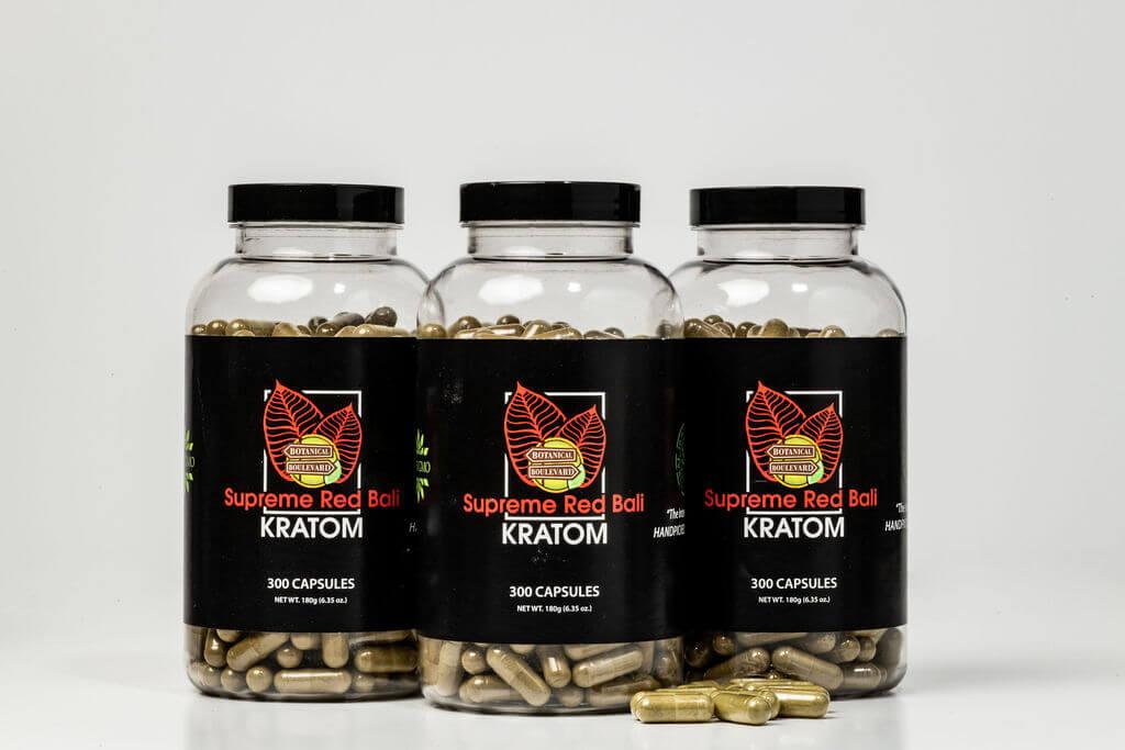 supreme red bali kratom capsules on tabletop