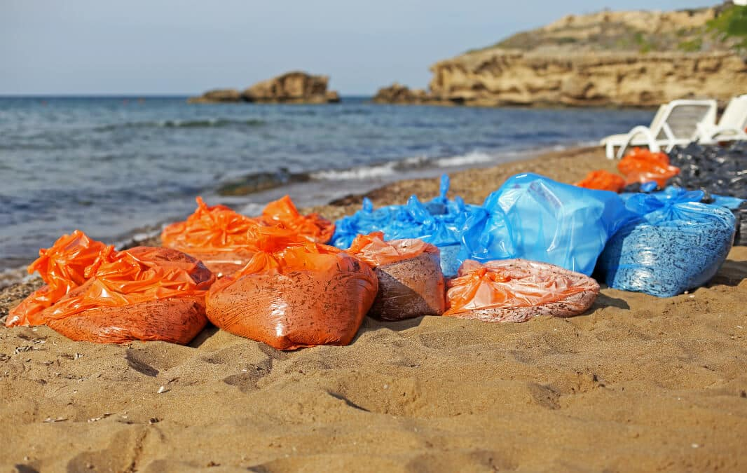 orange and blue garbage bags at the beach