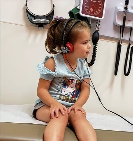 Young girl sitting in exam room with headphones on Aural Habilitation