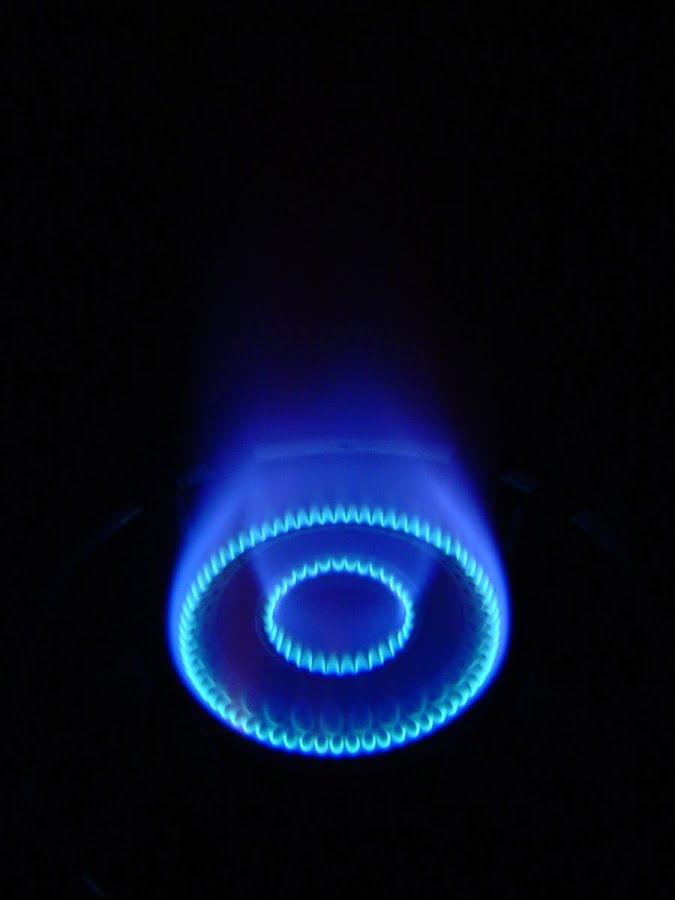 An image of a Gas burner, fill with holes that excretes blue flame