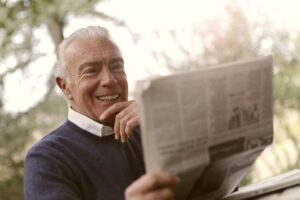 An older man with white hair reads a newspaper.