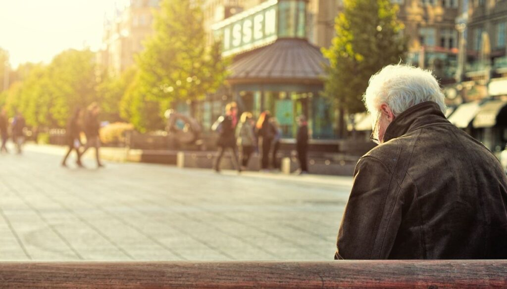 A man sits on a brown wooden bench facing away from the camera. Photo by Huy Phan for Unsplash.