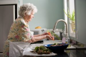 An older woman washes vegetable in a stainless steel kitchen sink. Photo by CDC on Unsplash.