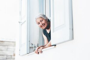 A senior-aged woman peers out her balcony window, smiling. Photo by Nick Karvounis on Unsplash.