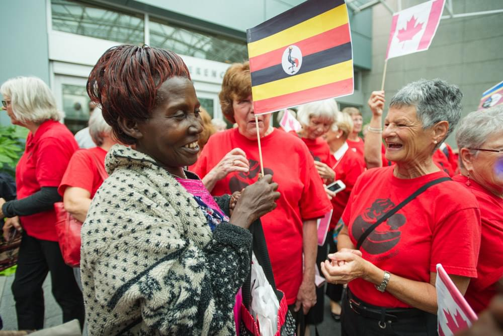african and canadian grandmothers smiling and gathering outside with flags