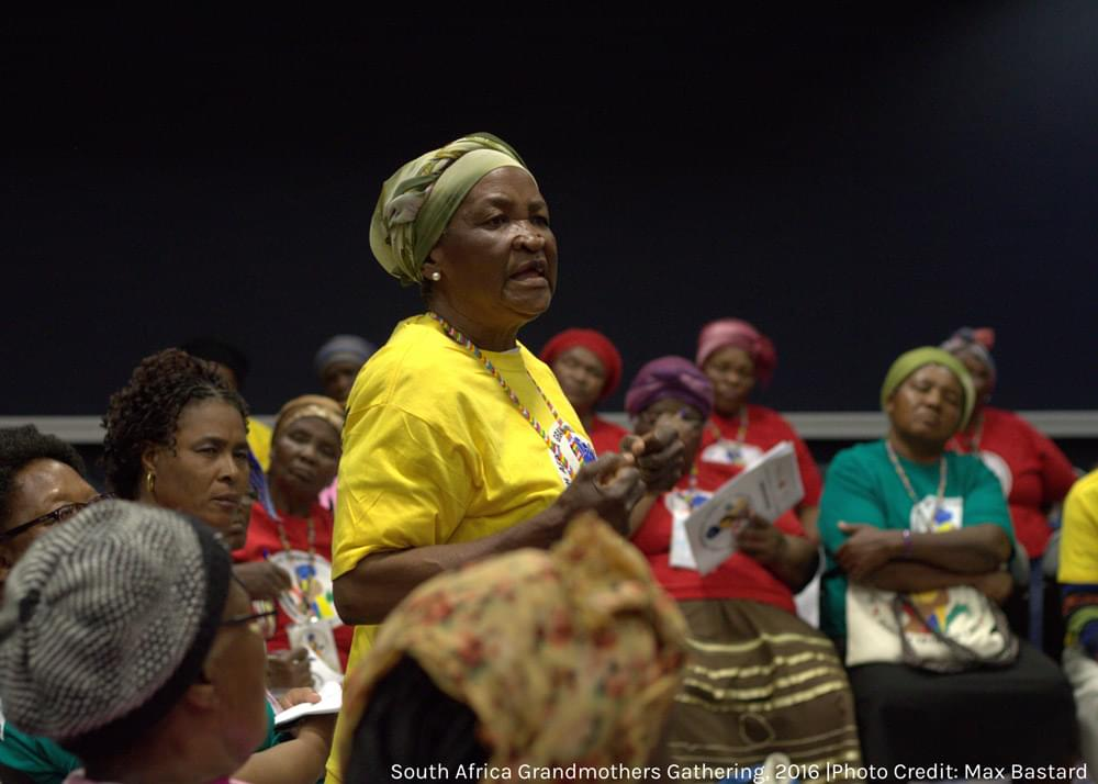 a woman speaking to a circle of grandmothers seated around her