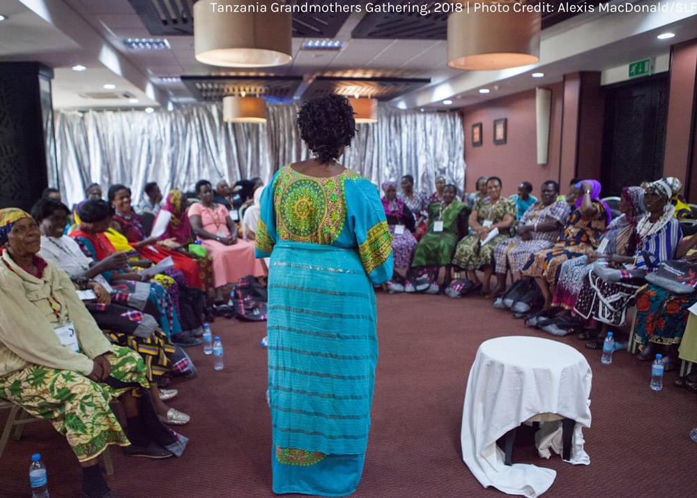 a woman standing and speaking to a circle of seated women